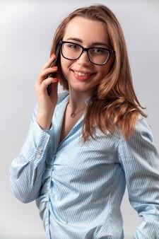 Bella ragazza in una camicia blu e occhiali parlando al telefono su uno sfondo bianco.