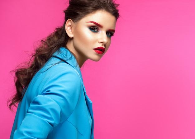 Bella ragazza in abito blu su sfondo rosa con trucco creativo e stile alla moda.