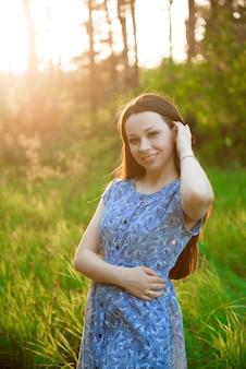 Bella ragazza in un vestito estivo blu nei raggi del tramonto nel parco.