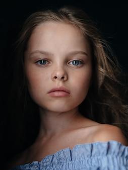 Una bella ragazza in un prendisole blu su capelli scuri e ricci