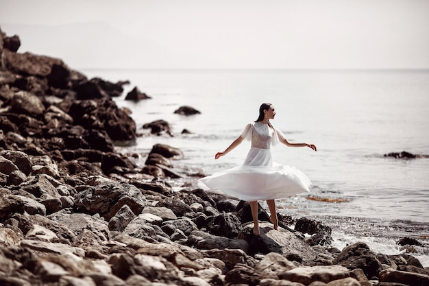 Una bella ragazza, una sposa, in un abito bianco, a piedi nudi sulle pietre