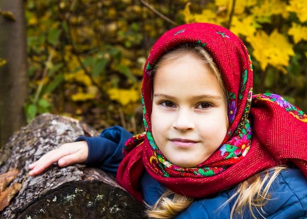 Bella ragazza in una sciarpa rossa brillante. ritratto di una ragazza con gli occhi marroni in una vecchia sciarpa russa sullo sfondo dell'autunno. servizio fotografico