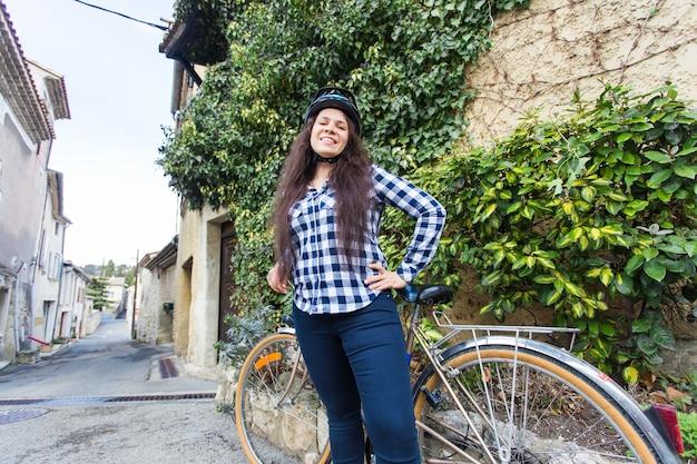 Una bella ragazza e una bicicletta in un vicolo stretto