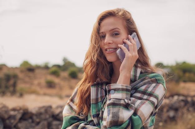 Una bella ragazza che chiama con il suo telefono