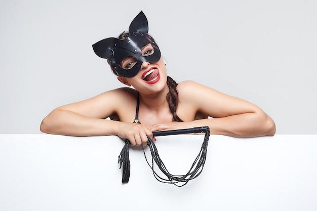 Bella ragazza in una maschera da gatto. indica lo spazio libero per il testo.