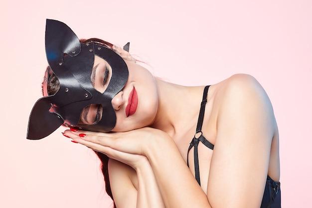 Bella ragazza in una maschera da gatto. in posa scherzosamente