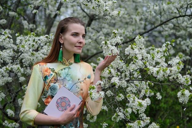 Bella ragazza in fiori di ciliegio vestito cinese