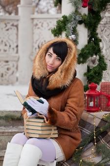 Bella ragazza in un gazebo decorato a natale con un cappotto di pelle di pecora legge libri