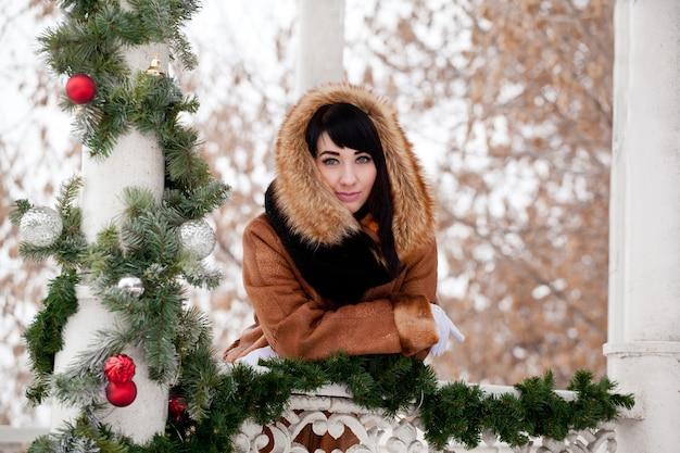 Bella ragazza in un gazebo decorato a natale con un cappotto di pelle di pecora