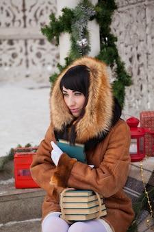 Bella ragazza in un gazebo decorato a natale in un abito bianco e un cappotto di pelle di pecora in un abbraccio con i libri