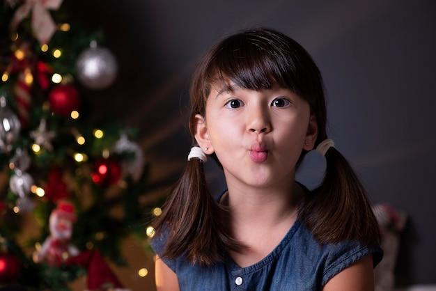 Bella ragazza nella decorazione di natale che soffia bacio