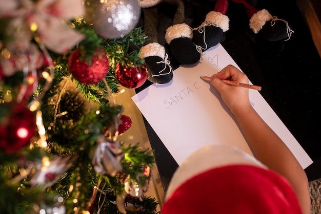 Bella ragazza nella decorazione di natale scrivendo la lettera a babbo natale