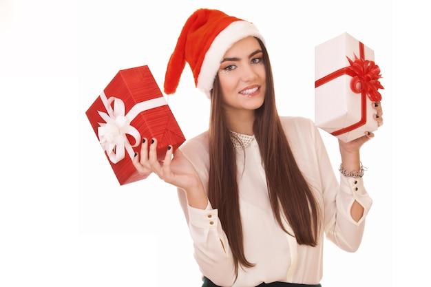 Bella ragazza in cappello di natale e con due scatole regalo in mano