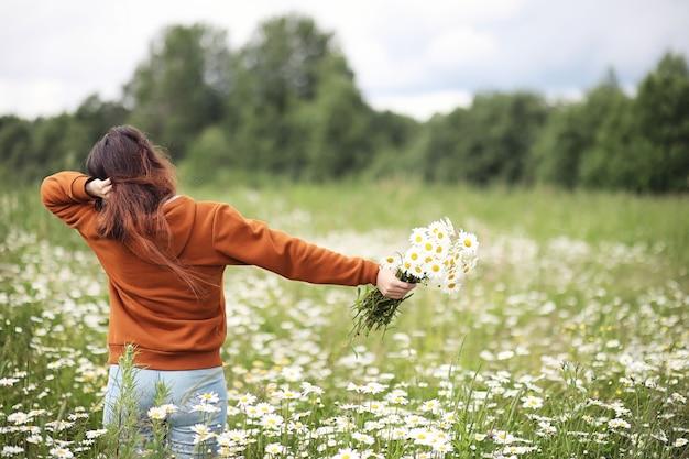 La bella ragazza raccoglie le margherite nel giorno di estate in afield