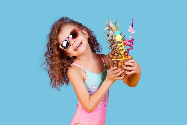 Bella ragazza in costume da bagno colorato e occhiali da sole che tengono pinea