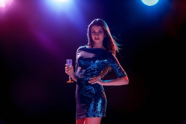 La bella ragazza che balla alla festa bevendo champagne