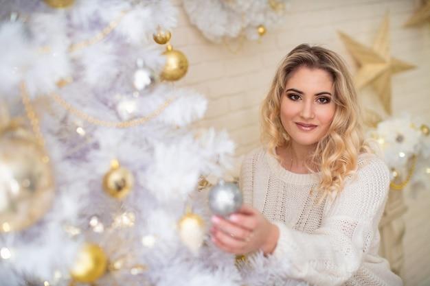 Bella ragazza che decora l'albero di natale. una giovane donna sorridente prepara un albero di natale per le vacanze. bionda in una camicetta leggera. albero di natale bianco lussureggiante con palline d'oro