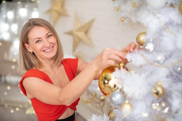 Bella ragazza che decora l'albero di natale. una giovane donna sorridente prepara un albero di natale per le vacanze. bionda in abito rosso. albero di natale bianco lussureggiante con palline d'oro