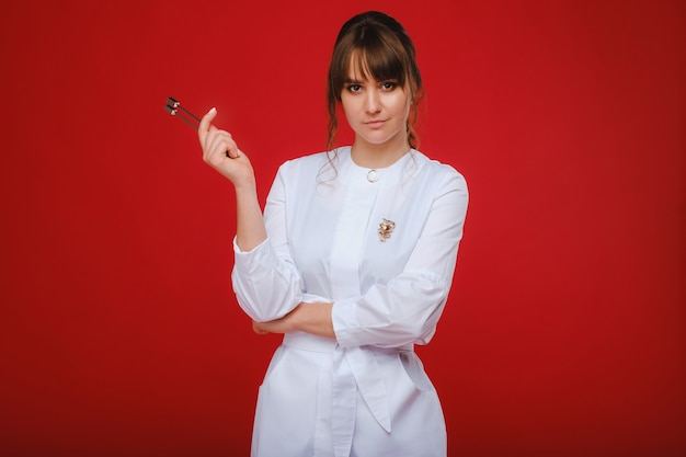 Bella ragazza medico con un diapason.