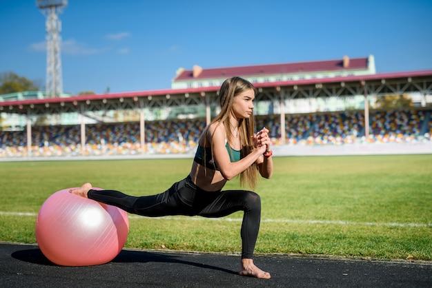 Bella ragazza che fa esercizi su fitball allo stadio in una giornata di sole. stile di vita sano in città.