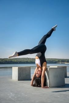 Bella ragazza che fa una posa di yoga la mattina presto prima dell'orario di lavoro. stile di vita sano