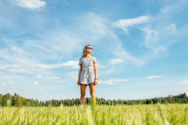 Bella ragazza in vestito sul campo verde