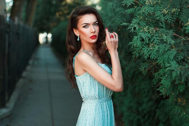 Bella ragazza in un vestito con orecchini vicino al cespuglio verde