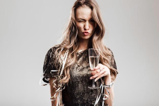 La bella ragazza vestita in vestito nero elegante ed elegante tiene un bicchiere di champagne che fa smorfie su uno sfondo bianco.