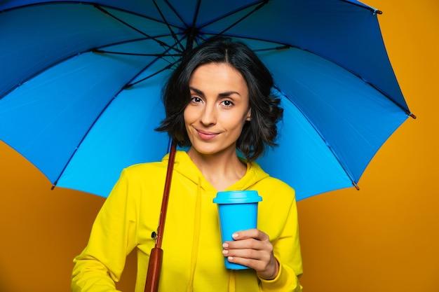 Bella ragazza vestita con una felpa gialla sotto un ombrello, tenendo la tazza blu nella mano sinistra, divertendosi.