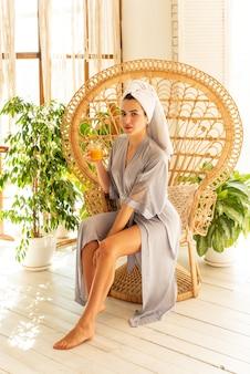Una bella ragazza in vestaglia beve succo d'arancia. saluta magnificamente la sua mattina prendendosi cura di se stessa