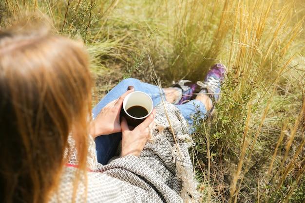 Bella ragazza che beve caffè nella natura autunnale. una tazza con bevanda calda in montagna. umore accogliente. foglie rosse e gialle. autoisolamento durante il periodo di quarantena. pensa alla vita.