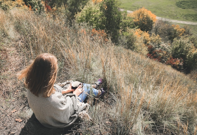 Bella ragazza che beve caffè nella natura autunnale. una tazza con bevanda calda in montagna. umore accogliente. foglie rosse e gialle. coperta alla moda sulle spalle della donna. vista dalla collina.