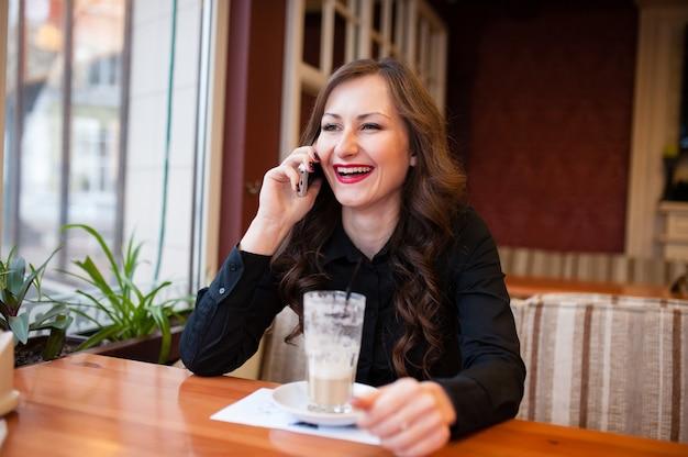 Bella ragazza che beve caffè e parla al telefono