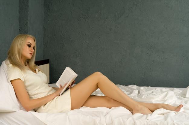 Una bella ragazza durante una pandemia di autoisolamento legge un libro sdraiata su un letto a casa.
