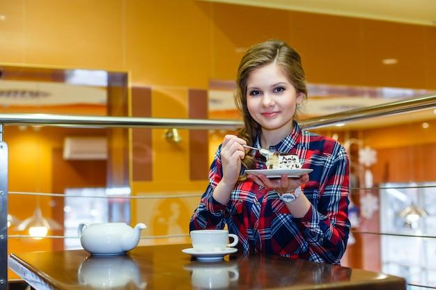 Bella ragazza che mangia la torta nel caffè