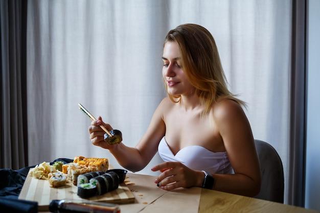 Bella ragazza che mangia il primo piano dei sushi. rotolo di sushi sorridente della tenuta della donna con le bacchette. cibo giapponese sano.
