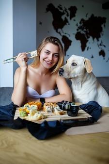 Bella ragazza che mangia il primo piano di sushi con il suo cane labrador, sorridente, in possesso di un rotolo di sushi con le bacchette. cibo giapponese sano.