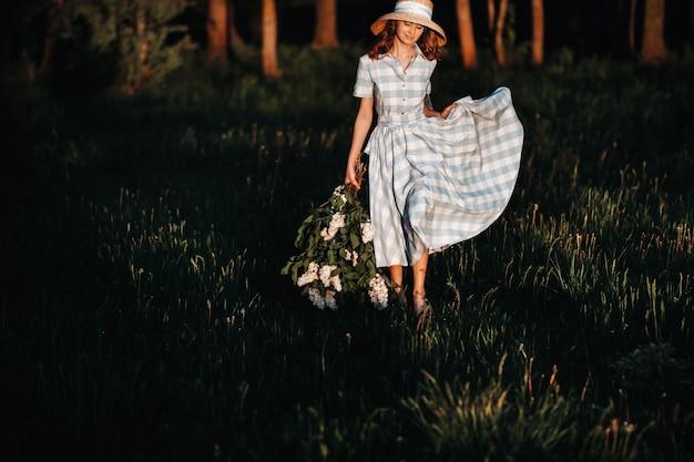 Bella ragazza che gode dell'odore del lillà in una giornata estiva. aromaterapia e concetto di primavera.