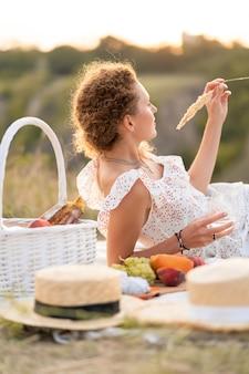 La bella ragazza gode di un picnic al tramonto in un posto bellissimo.