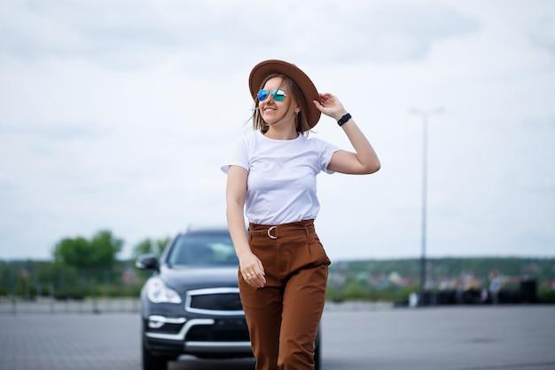 Una bella ragazza di aspetto europeo con gli occhiali e un cappello marrone si trova vicino a un'auto nera. servizio fotografico vicino alla macchina.