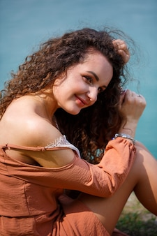 Una bella ragazza di aspetto europeo con i capelli ricci e un sorriso sul viso siede in un prato verde sullo sfondo di un lago blu. calda giornata estiva, giovane donna felice, emozioni di gioia