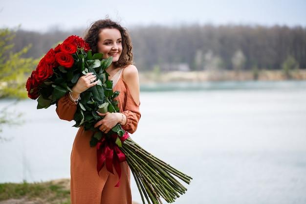 Una bella ragazza di aspetto europeo con i capelli ricci e un sorriso sul viso con un enorme mazzo di rose rosse su uno sfondo di lago blu. calda giornata estiva, giovane donna felice, emozioni di gioia