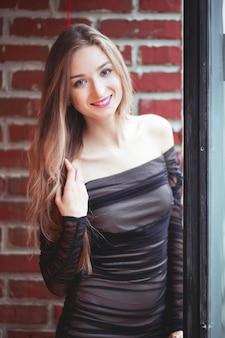 Bella ragazza in un abito da sera in posa contro un muro di mattoni