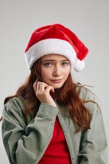 Bella ragazza in un cappello festivo con un pompon tiene la mano vicino al viso