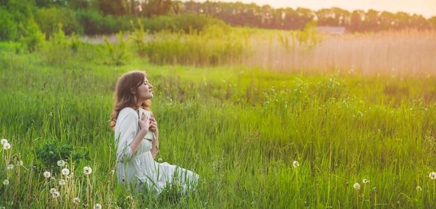 Bella ragazza in campo leggendo un libro. la ragazza seduta su un prato, leggendo un libro. riposo e lettura