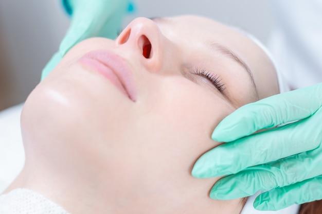 La bella ragazza ottiene il peeling del viso. concetto di salute della pelle. saloni di bellezza. tecnica mista
