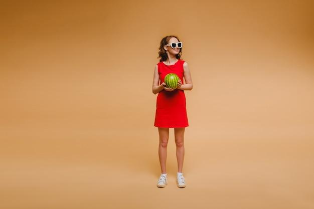 Una bella ragazza con gli occhiali e un vestito rosso tiene in mano un'anguria.
