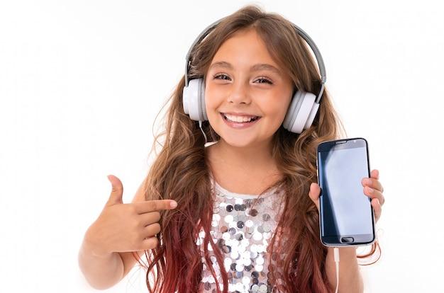 Bella ragazza in abito luccicante, con grandi cuffie bianche che ascolta la musica e che mostra lo schermo dello smartphone nero e che punta a esso isolato