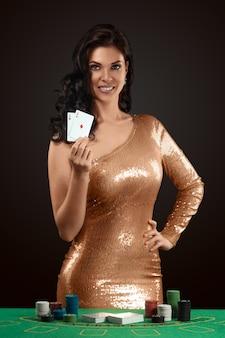 Una bella ragazza in un abito da croupier splendente d'oro tiene in mano due carte da gioco davanti a sé