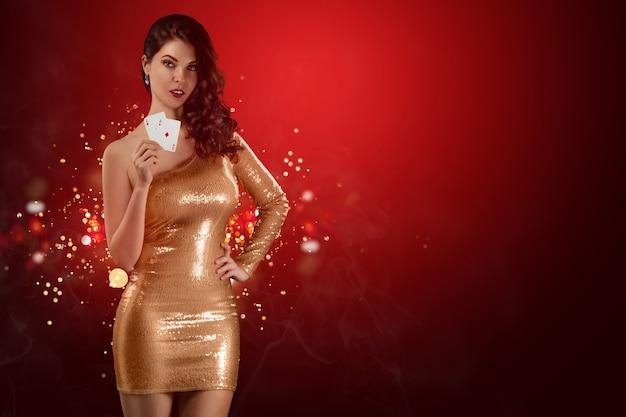 Bella ragazza in un vestito da croupier lucido dorato che tiene in mano due carte da gioco sul rosso